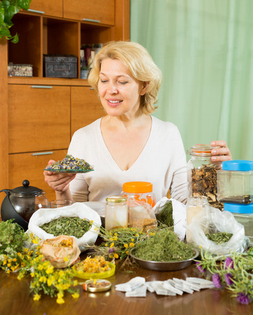 heterogeneous: Senior  woman doing herbal tea and smiling