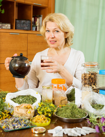 mature woman with herbal tea and herbs