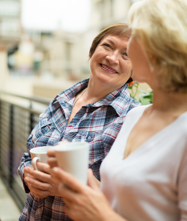 retirement homes: Two mature housewives with cup of tea at terrace with decorative plants