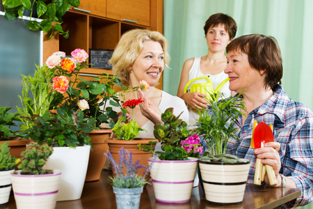 flowerpots: mature women  and girl near table with many flowerpots