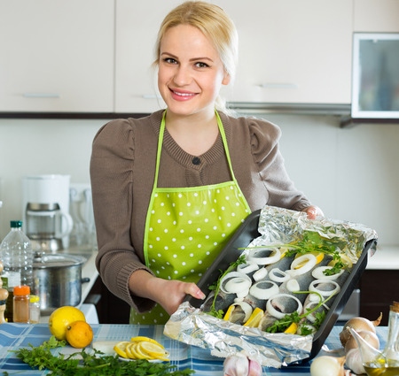 panful: Happy smiling blonde woman cooking fish with lemon in kitchen at home Stock Photo