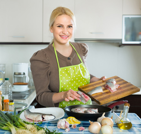 fryingpan: Happy smiling woman putting pieces of fish in frying pan at home kitchen Stock Photo
