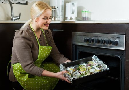 fryingpan: Ordinary woman cooking fish  in oven at home kitchen Stock Photo