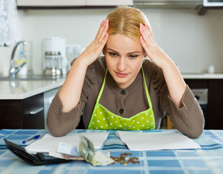 parsimony: Sad woman calculating the family budget at  home Stock Photo
