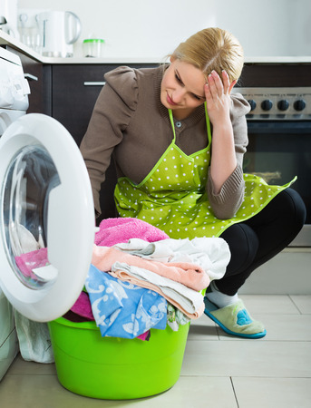 unsatisfactory: Tired young woman doing laundry with washing machine at home kitchen