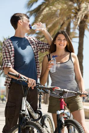 or thirsty: Pareja joven sedienta en bicicletas de tomar una bebida refrescante de agua de la botella