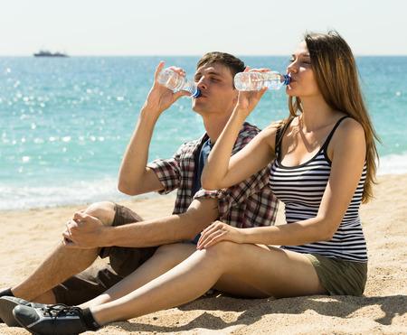 sediento: Pareja joven sedienta disfruta de una bebida refrescante de agua en un d�a soleado Foto de archivo
