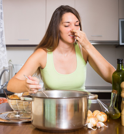 odour: Unhappy woman preparing exotic food with rank odour