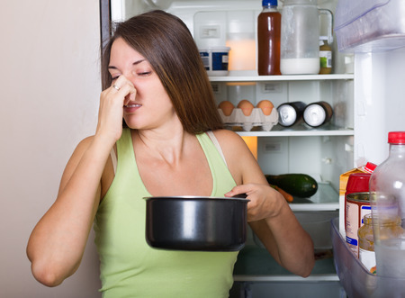 frowy: Young woman holding foul food near open  refrigerator at home