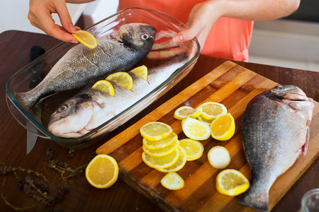 fryingpan: Close-up of woman putting pieces of lemon in fish at home kitchen