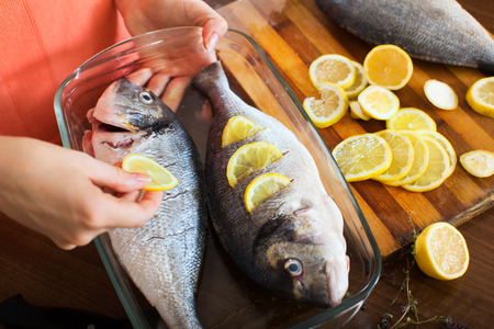 Close-up of housewife putting pieces of lemon in fish at home kitchen