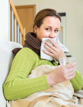 linctus: Portrait of sick woman being treated for cold  on sofa at home