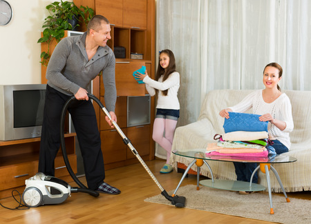 Happy smiling girl helping happy parents to clean at living room. Focus on man photo