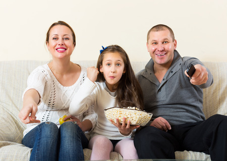 clothes interesting: Cute girl and happy parent sitting with popcorn in front of TV