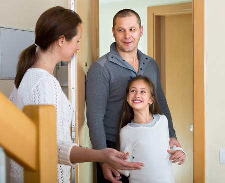 inviting: Happy woman standing at doorway and inviting guests to come inside. Focus on girl Stock Photo