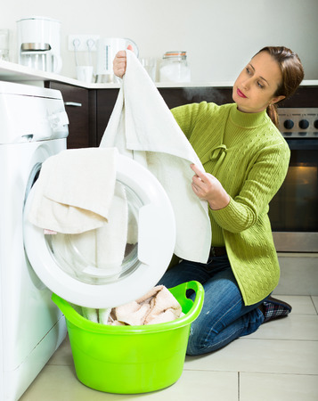 unsatisfactory: Home laundry. Tired housewife in green using washing machine at home