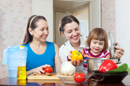 Happy family together cooking lunch with vegetables photo