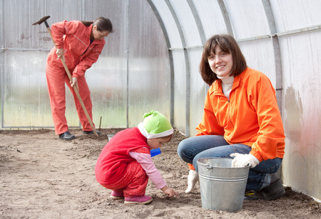 hothouse: Happy women with child works at hothouse in spring