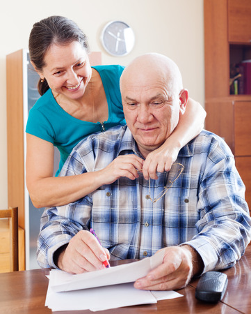 mature couple fills in paper documents together at home photo