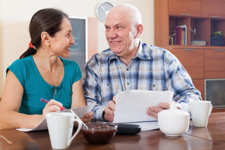 Happy senior couple holding financial documents photo