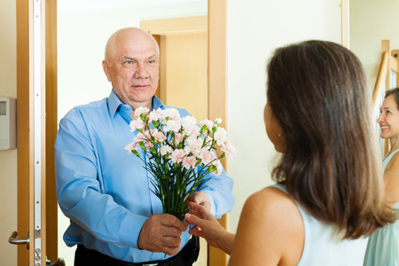 at came: Senior man came to mature woman with flowers at home door