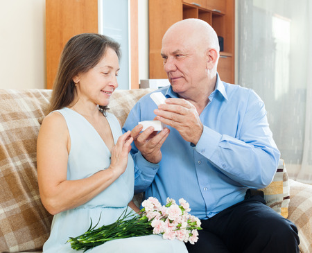 jewel box: Mature man giving  wife the  jewel box  at home Stock Photo