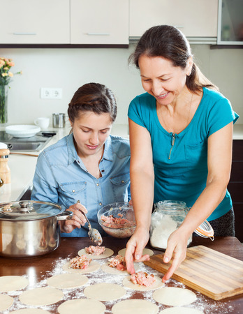 stuffing: Two women making meat dumplings from stuffing and dough