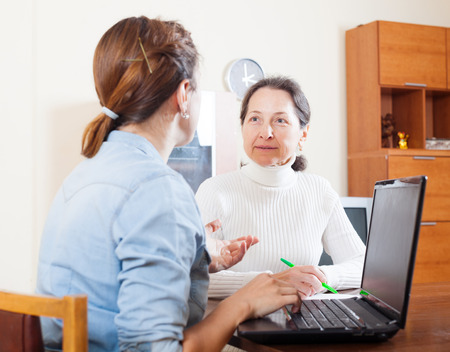 outreach: Mature woman answer questions of outreach worker in home