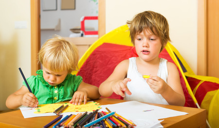 gladful: Siblings  together with pencils in home interior