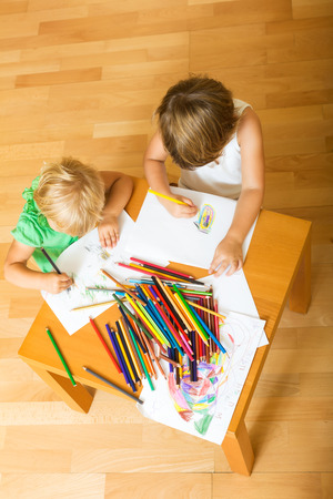 two year: Two year children together with pencils in home interior Stock Photo