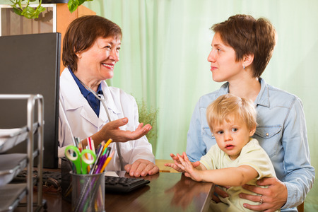 auscultoscope: Mother with toddler talking with female pediatrician doctor at clinic Stock Photo