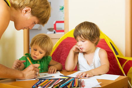 gladful: Mother and children playing with pencils at home