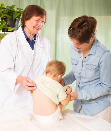 auscultoscope: friendly pediatrician doctor examining baby girl with stethoscope at clinic office