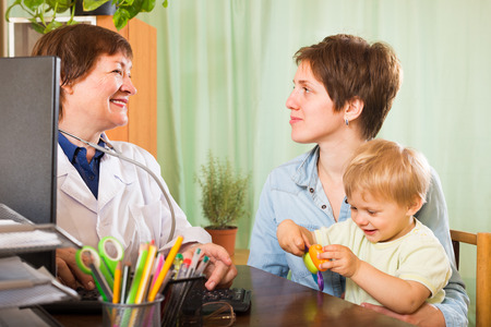 general pediatrician: Smiling aged female pediatrician doctor at the table examining toddler at clinic office