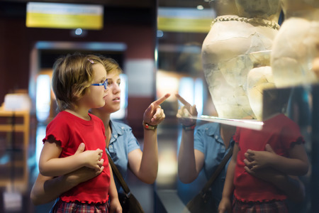 exhibitions: Woman and child looking old ancient amphora in historical museum