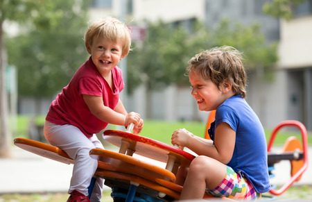 playground children: Happy little girls having fun at playground in sunny day