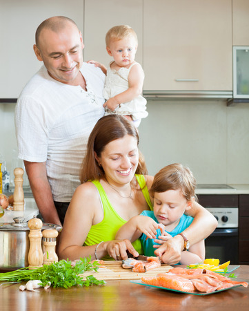 20 23 years: Happy family of four in the kitchen preparing seafood