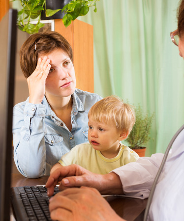 general pediatrician: woman with baby listening friendly pediatrician doctor at clinic Stock Photo