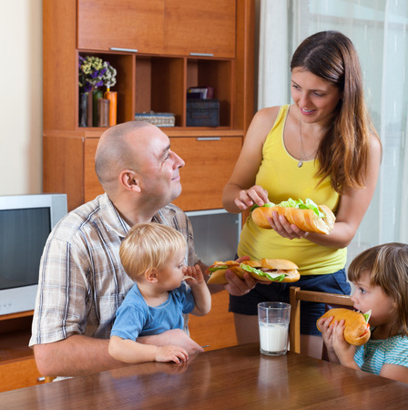 gladful: Happy family of four regular dinner at a table with sandwiches