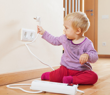 Toddler playing with electrical extension and outlet on floor at home photo
