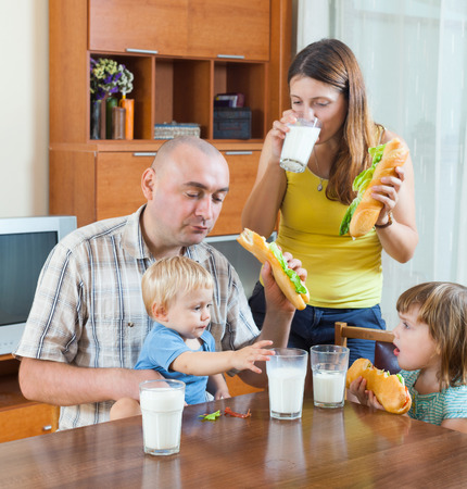 gladful: Happy family of four with dinner eating sandwiches on the table in the house