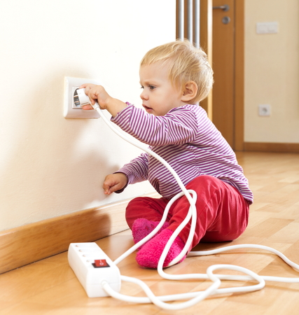 riskiness: Toddler playing with  electric equipment on floor at home