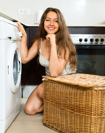 clothes washer: young girl washing clothes in washer at home