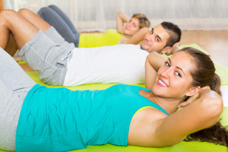 european people: Positive adults at group doing exercises in fitness club. Focus on girl
