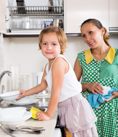 Daughter with smiling mother washing dishes in kitchen photo