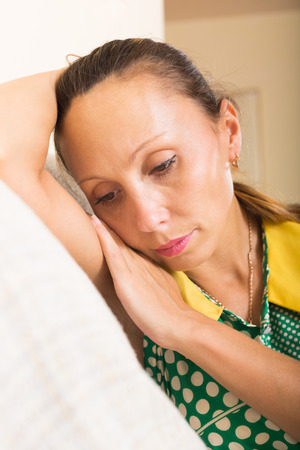 heartbreak issues: Portrait of sad middle-aged woman on sofa at home