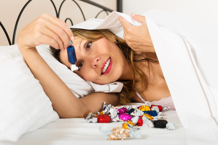 lier: Woman resting with sweet candy under blanket and smiling
