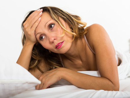 ennui: Sad middle-aged woman laying in bed with dropped eyes