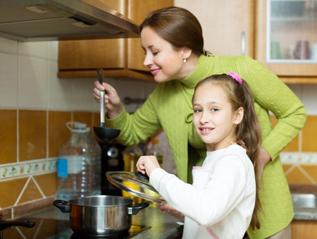 adult child: child with her adult mother prepare the soup by the stove in his kitchen. Focus on the child