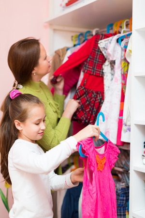 cloakroom: Smiling little daughter and mom choosing apparel in cloakroom